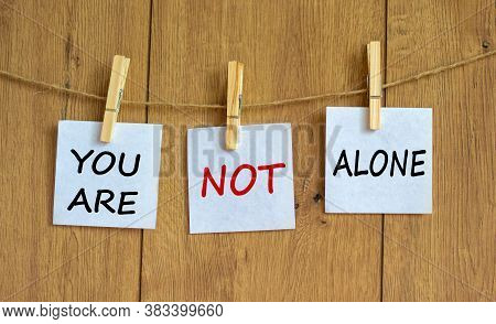 Wooden Clothespins With White Sheets Of Paper. Text 'you Are Not Alone'. Beautiful Wooden Background
