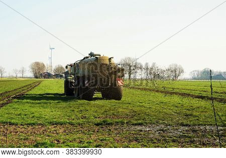 Tractor In March Drives Manures On The Field