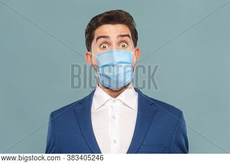 Closeup Portrait Of Surprised Or Shocked Young Man With Surgical Medical Mask Looking At Camera With