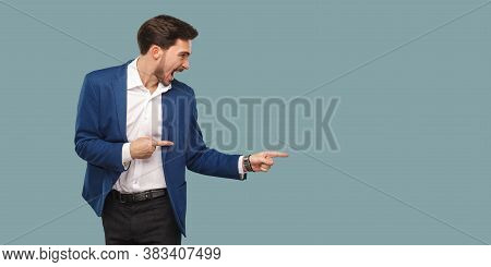 Handsome Amazed Bearded Man In Blue Suit Standing And Pointing At Background And Screaming And Looki