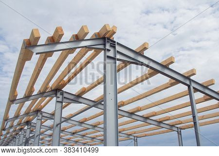 Wooden Roof Beams On The Steel Frame Of A Building Under Construction. Construction Of An Agricultur