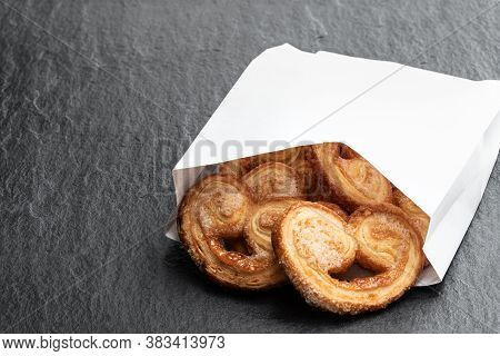 Flaky  Pastry Hearts Glazed With Caramelized Sugar In Paper Bag On Black Stone Background