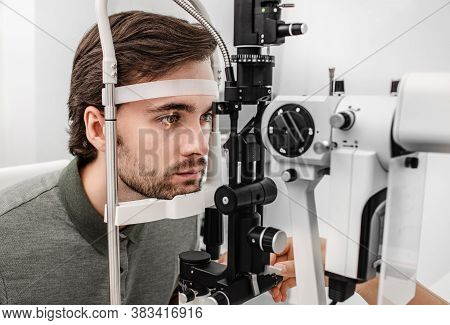 Adult Man Getting An Eye Exam At Ophthalmology Clinic. Checking Retina Of A Male Eye Close-up
