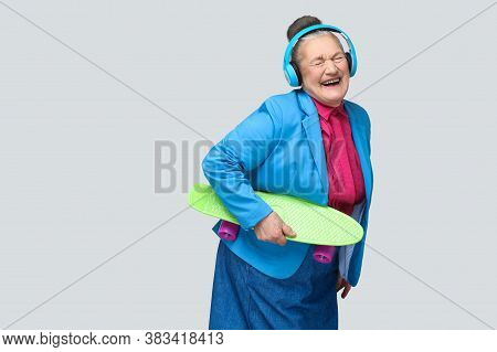 Trendy Funny Joyful Grandmother In Colorful Casual Style With Blue Headphones Holding Green Skateboa