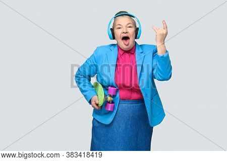 Trendy Funny Grandmother In Casual Style With Blue Headphones Holding Green Skateboard Listen Music
