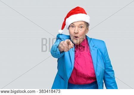Amazed Grandmother In Colorful Casual Style, Blue Suit And Christmas Red Cap Standing And Looking An