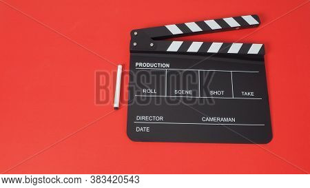 Pen With Black Clapperboard Or Movie Slate Use In Film Production And Cinema Industry On Red Backgro