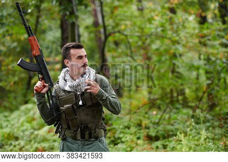 terrorist have a break and smoke cigarette in forest during battle