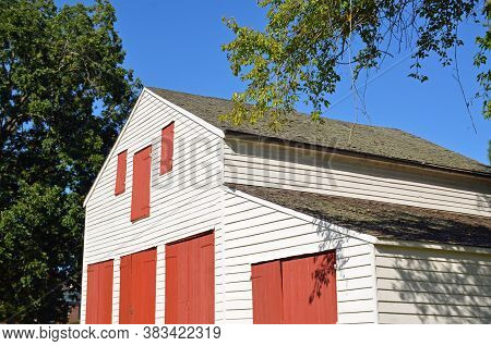 NATCHEZ, MS - August 24, 2020 Located in the Natchez National Park, the carriage house at Melrose estate, part of one of the most intact antebellum properties in the South, pops with red painted doors against white walls.
