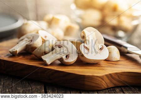 Fresh white champignon mushrooms on cutting board.