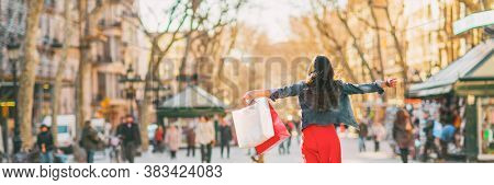 Shopping fun happy woman with bags spending buying new clothes in stores of Barcelona, Spain. Panoramic banner of happy girl with open arms in freedom.
