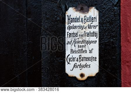 A White Old Danish Sign On A Black Wall, Panhandling Forbidden, Faaborg, Denmark, August 16, 2020