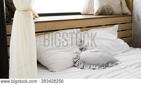 Bed In The Bedroom At The Window With Textured Coverlets With Plaids And Pillows