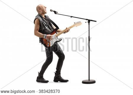 Bald punk rocker singing on a microphone and playing a guitar isolated on white background