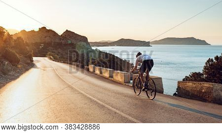 Man Cyclist Pedaling On A Road Bike Outdoors In Sun Set