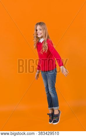 Girl In Red Sweater And Jeans Stand On Tiptoe. Child Smile With Curly Blond Hair On Orange Backgroun