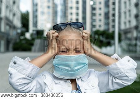 Little Blond Caucasian Girl Wearing Protective Face Mask Feel Stressed And Unhappy Screaming And Cry