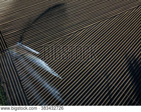 Intense agriculture fiekd being irrigatedwith huge amounts of water on a hot summer day - aerial image