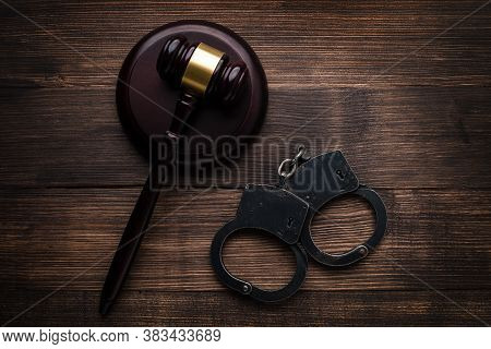 Handcuffs And Judge Gavel On Brown Table, Gavel With Stand And Handcuffs On A Wooden Background Top