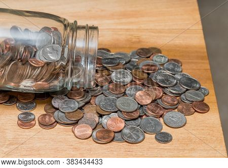 Hundreds Of Us Coins Pouring Out Of Savings Jar On Wooden Table As Concept For Shortage Of Loose Cha
