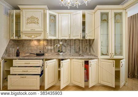 Front view of luxury modern neoclassic beige kitchen interior, most doors are open