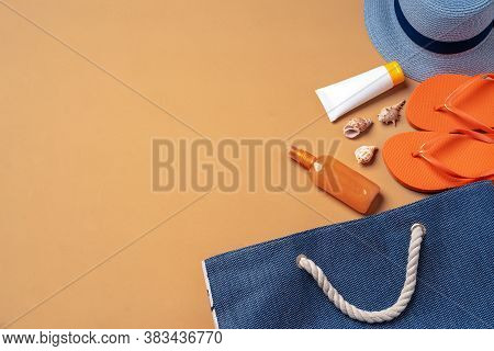 Beach Bag With Suntan Products, Flip-flops And Hat On Beige Background