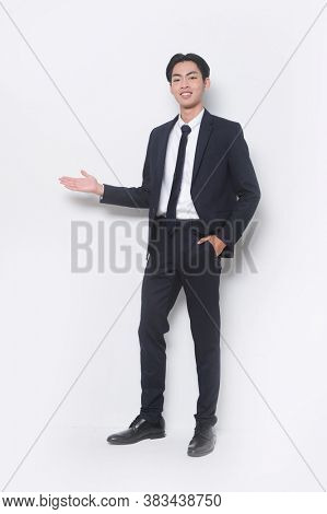 Men's beauty, fashion. Handsome full body young businessman wearing black suit and black pants , tie,black shoes with welcome gesture