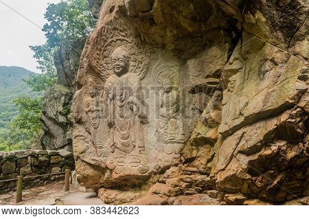 Seosan, South Korea; August 26, 2020: Rock-carved Triad Featuring Buddha, Standing Bodhisattva, And