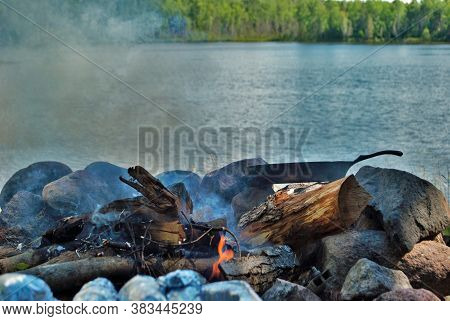Cooking On A Cast-iron Skillet Over A Camp Fire Next To The Lake