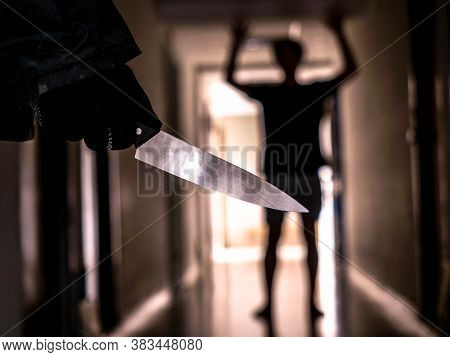 Hand With Knife Following Young Terrified In The Apartment. Man Bandit Is Holding A Knife In Hand, T