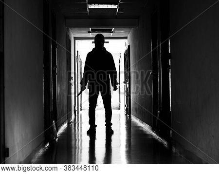 Man Silhouette Walking Away With Knife In The Light Of Opening Door In Dark Room, Threat Concept.
