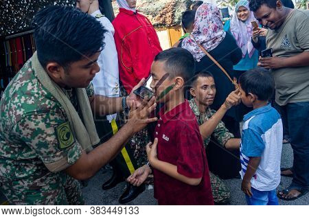 Georgetown, Penang/malaysia - Feb 29 2020: Soldier Help Child Make Up Camouflage During Malaysia Arm