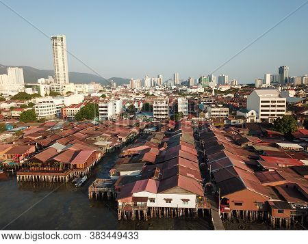Georgetown, Penang/malaysia - Feb 29 2020: Wooden House At Sea Clan Jetty. Background Is Komtar Towe