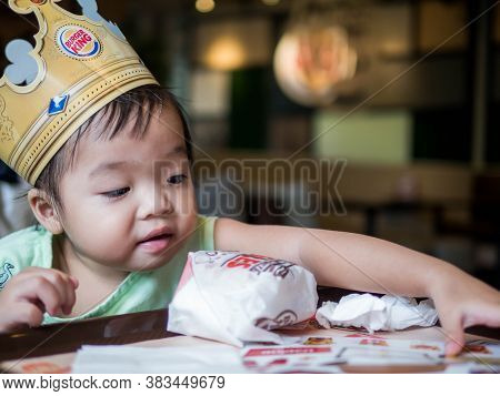 Bangkok Thailand, 2018: Little Girl With A Cardboard Crown At Burger King Restaurant. Burger King Is