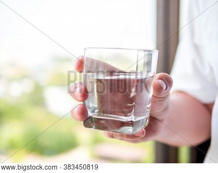 Hand Of Man Holding A Clear Glass Of Water For Drinking In The Morning