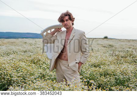 Tall Handsome Man Standing In The Middle Of Camomile Flowers Field And Holding White Chair On His Sh