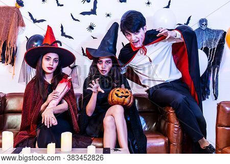 Asian Happy Friends Sitting On Sofa In Costumes And Makeup On A Celebration Of Halloween Posing With