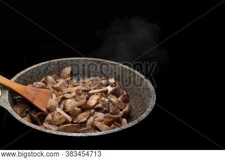 Close-up Of A Wooden Spoon And Fried Or Stewed Mushrooms In A Skillet, Steam Rises From Hot Mushroom