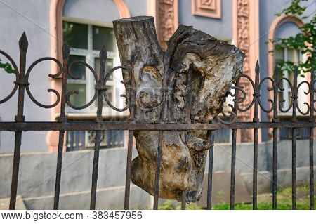 A Sawn Piece Of Wood Stuck In A Metal Fence