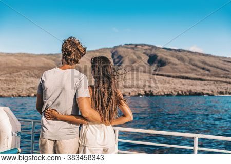 Cruise vacation couple tourists in love whale watching at sunset on ship deck outside. Happy travel vacation lifestyle.