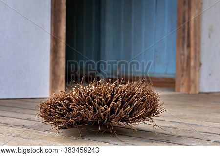 An Old Straw Broom Discarded On The Floor Of An Abandoned Country Building