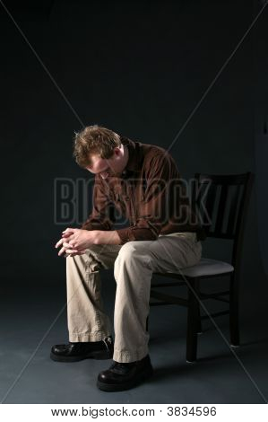Man Sitting In Chair With Head Down  Looking Sad