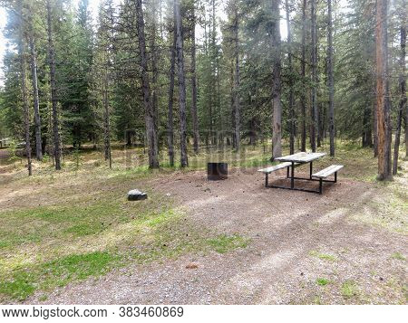 A Photo Of A Standard Campground With A Picnic Table, Firepit And Tentpad Area.  The Campground Is E