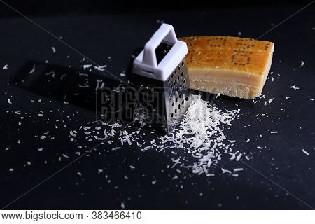Food grater and grated cheese parmesan are on the black background close up taken.