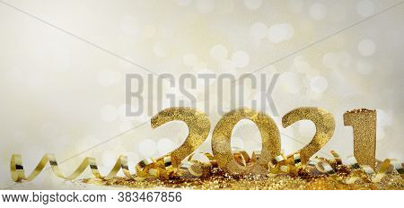 2021 Golden Figures In Glitter And Ribbon On Abstract Blur Light Background