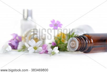 Close On Bottle Of Essential Oil Spilled And White End Pink  Petals Of Flowers On White Background