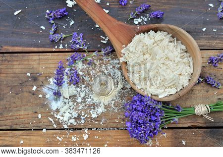 Spoon Full Of Flakes Of Soap With Essential Oil And Bunch Of Lavender Flowers On Wooden Background