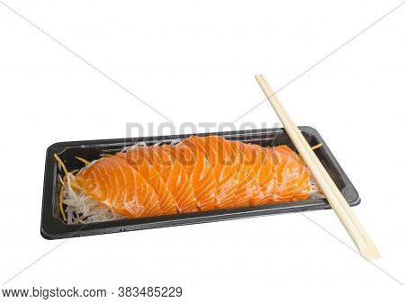 A Row Of Salmon Sashimi On Vegetable Slices In Small Black Tray, A Bamboo Chopsticks On Top, Salmon