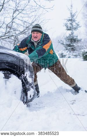 Winter, People And Car Problem Concept. Man Are Pushing The Car, Stuck In The Snow. Mutual Aid. Wint