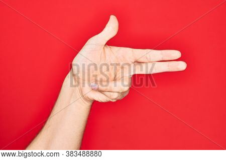 Hand of caucasian young man showing fingers over isolated red background gesturing fire gun weapon with fingers, aiming shoot symbol